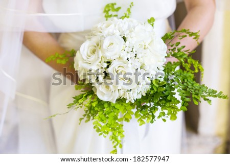 closeup bride holding bouquet of white roses - stock photo