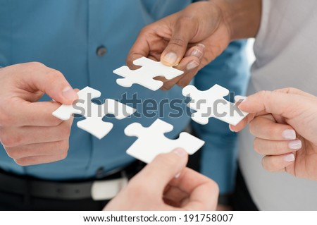 Closeup Businesspeople Hand Holding Jigsaw Puzzle - stock photo