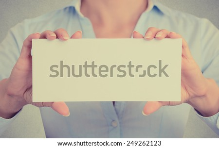 Closeup businesswoman hands holding white card sign with blank copy space for advertisement text message isolated on grey wall office background. Cropped retro instagram style image - stock photo