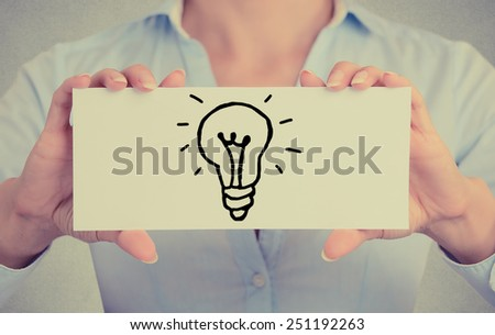 Closeup businesswoman hands holding white card sign with hand drawn illuminated light bulb isolated on grey wall office background. Retro instagram style image - stock photo