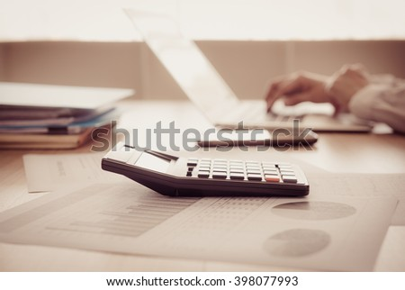 Closeup calculator on business and financial report with business people are analyzing growth business. Accounting concept. vintage style. - stock photo