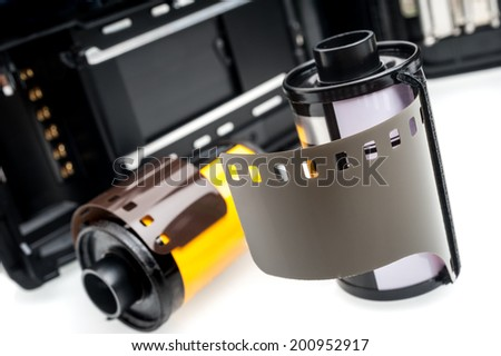closeup camera film and black camera with opened back lid on white background - stock photo