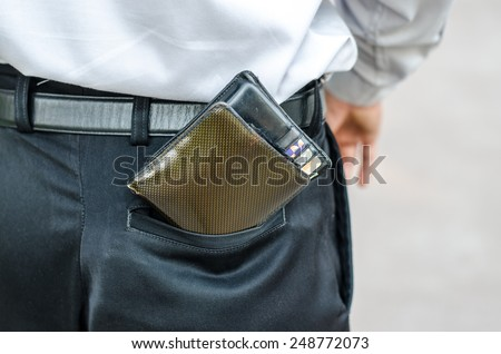 Closeup. Careless man with wallet falling back pocket. Risk of theft. - stock photo