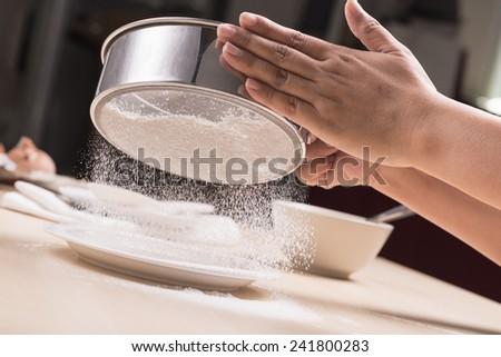closeup cook's hand powdering flour - stock photo