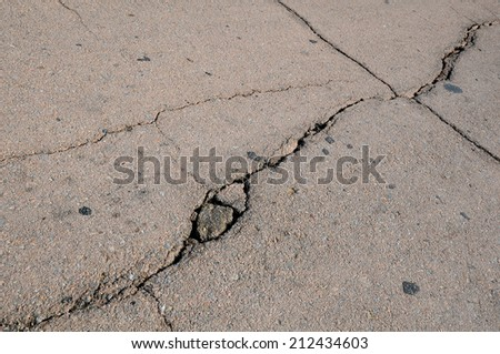 Closeup cracked asphalt pavement - stock photo