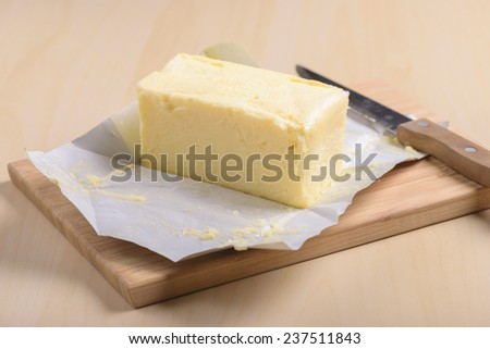 closeup creamy butter in its unwrapped foil paper - stock photo