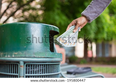 Closeup cropped portrait of someone hand tossing cash dollar bills money, hundred dollar bills in trash can, isolated outdoors green trees background. Bad financial investment decisions concept - stock photo