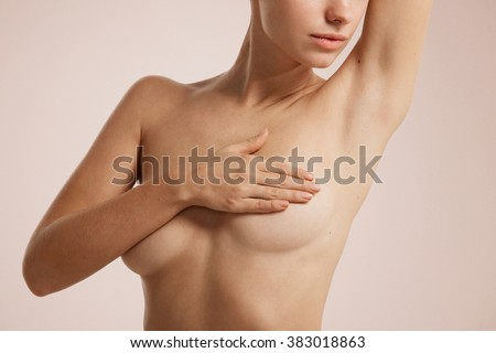 Closeup cropped portrait young woman with breast pain touching chest colored isolated on background - stock photo