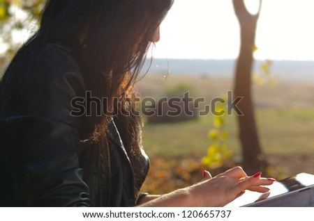 Closeup cropped side view of a woman using a tablet touching the screen with her finger against a background of open countryside - stock photo