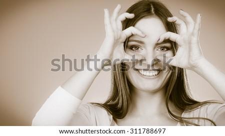 Closeup cute woman looking through imaginary binocular funny looking through fingers simulating glasses - stock photo