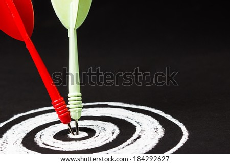 Closeup dart hit on the center of sketching dartboard  - stock photo