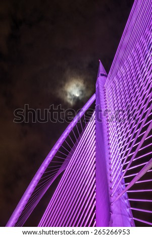 Closeup design of Sri Wawasan bridge at Putrajaya, Malaysia.  A night view showing pink color light on the steel structure with the moon and sky at the background. - stock photo