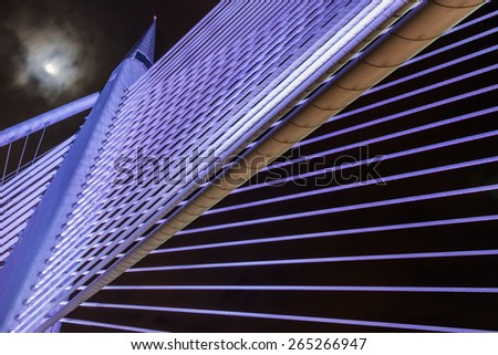 Closeup design of Sri Wawasan bridge at Putrajaya, Malaysia.  A night view showing purple color light on the steel structure with the moon and sky at the background. - stock photo