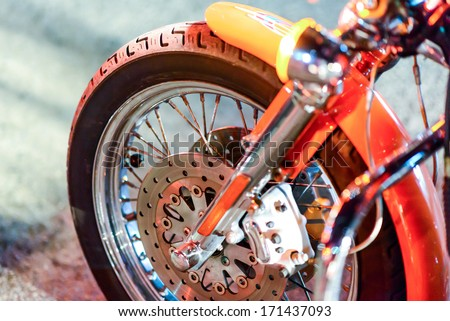 Closeup detail of a motorcycle's front wheel in traffic light - stock photo