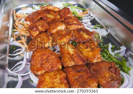 Closeup detail of grilled tawa fish curry on display at an indian restaurant buffet - stock photo