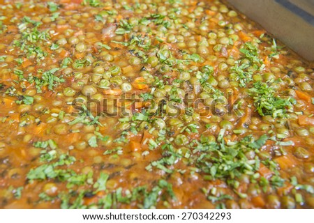 Closeup detail of peas with carrots in sauce on display at an oriental restaurant - stock photo