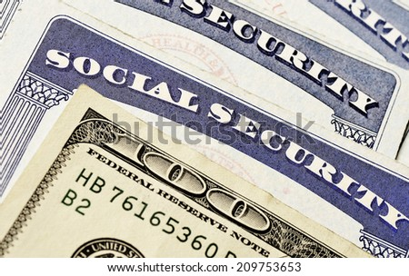 Closeup detail of several Social Security Cards and cash representing finances and retirement - stock photo