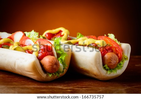 closeup detail of traditional homemade hotdogs with vegetables, ketchup and mustard - stock photo