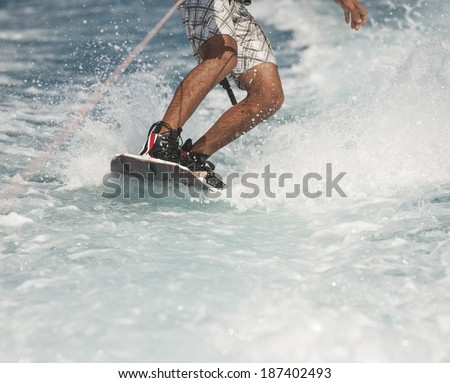 Closeup detail of wakeboarder on water behind speedboat - stock photo