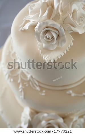 Closeup detail of white wedding cake at reception - stock photo