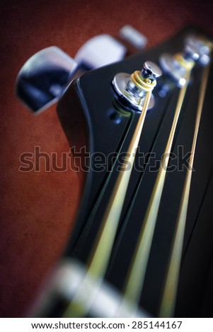 Closeup detail on an acoustic guitar head stock and metallic chord - stock photo
