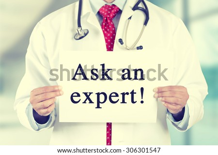 Closeup doctor hands holding white card sign with ask an expert text message isolated on hospital clinic office background. Retro instagram style filter image - stock photo