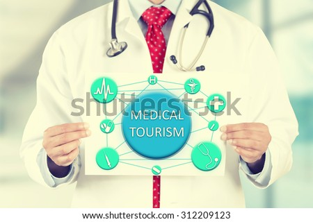 Closeup doctor hands holding white card sign with medical tourism text message isolated on hospital clinic office background. Retro instagram style filter image - stock photo