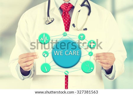 Closeup doctor hands holding white card sign with we care text message isolated on hospital clinic office background. Retro instagram style filter image - stock photo