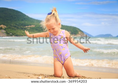 closeup European cute little blond girl with pigtail in swimsuit sits on sand near nice shell against wave surf - stock photo