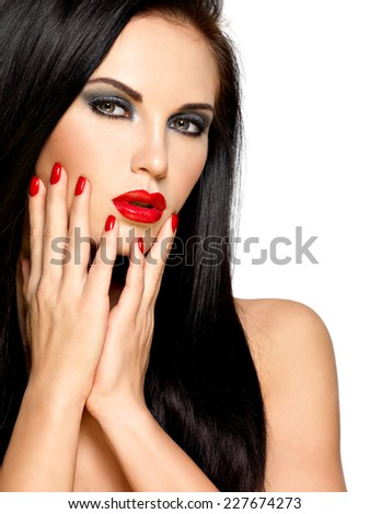 Closeup face of a beautiful brunette woman with red nails and lips - isolated on white background - stock photo