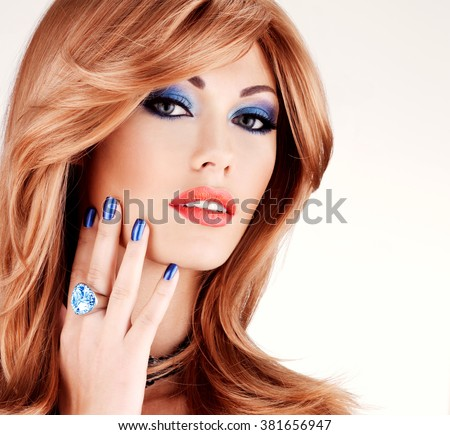Closeup face of a sensual beautiful woman with blue nails, blue makeup and sexy red lips  on white  background - stock photo