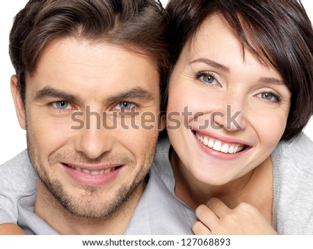 Closeup face of  beautiful happy couple isolated on white background. Attractive man and woman being playful. - stock photo