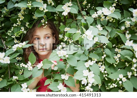 Closeup face of little girl looks out from blooming jasmine bush. - stock photo