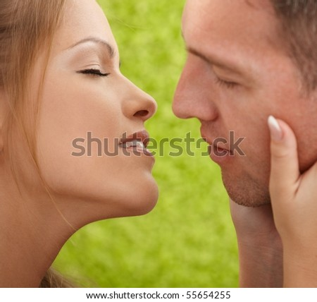 Closeup faces of affectionate couple about to kiss, woman holding man's face. - stock photo