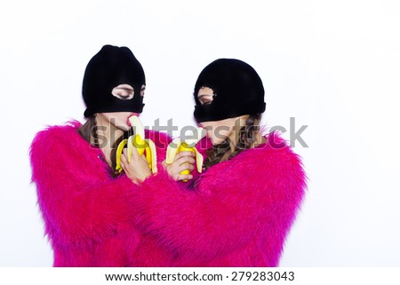 Closeup fashion lifestyle portrait of two pretty best friends girls eat bananas,wearing bright swag style pink fur,having fun and make crazy funny faces.Two sisters posing on party.Hipster.Swag style. - stock photo