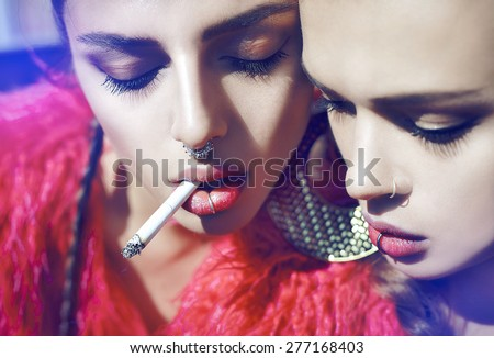 Closeup fashion lifestyle portrait of two pretty friends girls,wearing bright swag style pink fur,jewelry,having fun and make crazy funny faces and smoking.sisters posing on party.Hipster.Swag style. - stock photo