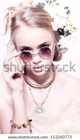 Closeup fashion portrait of beautiful teenager in jewelery flowers at hairstyle in pink glasses isolated - stock photo