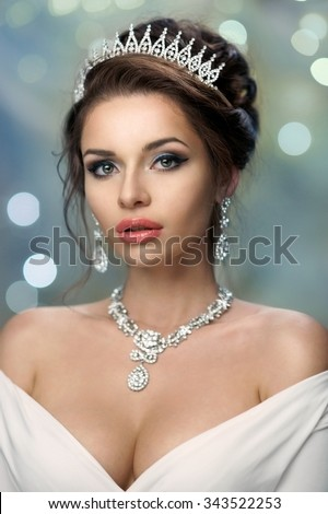 Closeup fashion portrait of young beautiful rich woman in dress with decollete and jewelry. Pretty girl wearing diadem, earrings and necklace. Bokeh background - stock photo