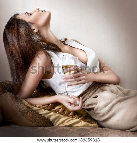Closeup fashion portrait of young sexy hot woman sitting relaxed on comfortable luxury sofa in vintage interior and drinking champagne or wine - stock photo