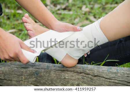 Closeup females injured ankle, getting bandage compression wrap - stock photo