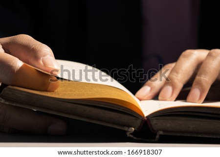 Closeup finger on the old book for reading concept - stock photo
