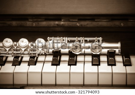 Closeup Flute on the keyboard of piano, musical instrument, vintage tone - stock photo