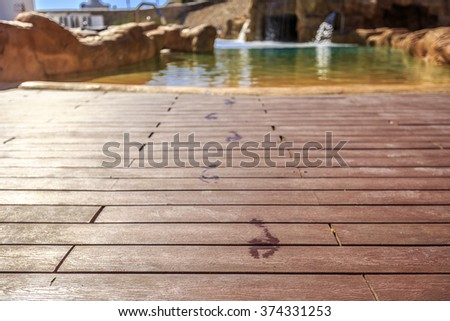 Closeup footprints on the wooden floor behind it swimming pool  - stock photo