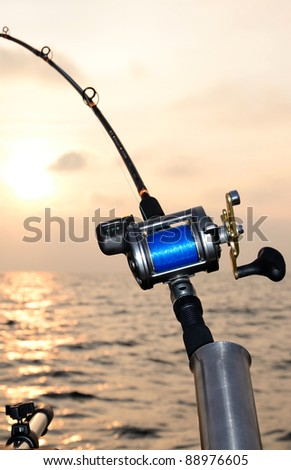 Closeup for fishing-rod at sunset - stock photo