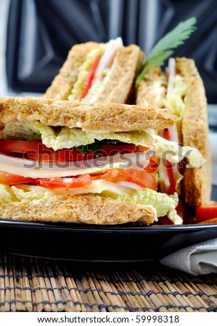 closeup fresh and delicious classic club sandwich over a black glass dish with coffee and toasters - stock photo