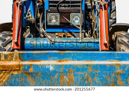Closeup frontal view of an old wheel tractor and part of its shovel bucket. Isolated against white background - stock photo