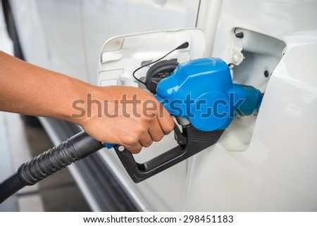 Closeup fueling blue fuel nozzle Car into Gas Tank - stock photo