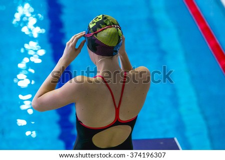 closeup girl preparing for swimming in stands on side of pool.view from back - stock photo
