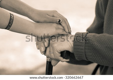 Closeup grandmother granddaughter holding hands, outdoors environment black and white edition. - stock photo