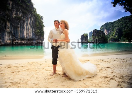 closeup groom blonde curly bride in fluffy dress stand join hands on edge of sand beach against azure sea green cliff - stock photo